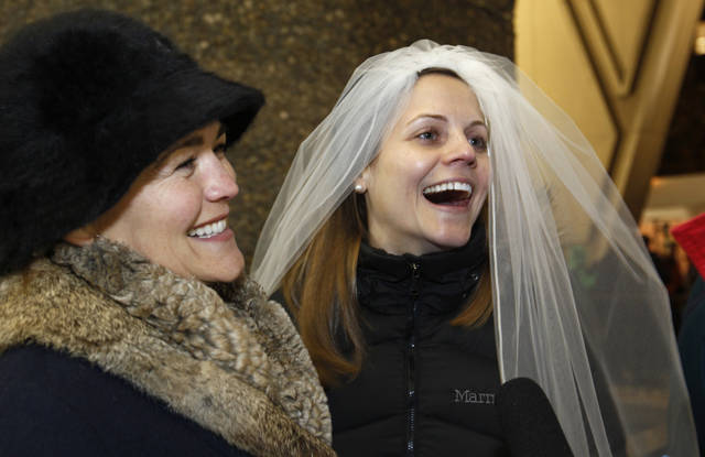 Amy Andrews, right, smiles as she wears a veil while standing in line with her partner Jeri Andrews while waiting to be among the first to be issued a marriage license to a same-sex couple, Wednesday, Dec. 5, 2012, in Seattle. King County Executive Dow Constantine was to began issuing the licenses just after midnight, immediately upon certification of the November election that passed Referendum 74 allowing same-sex couples to wed. Amy Andrews wore the same veil during a symbolic, though not legal, marriage ceremony the couple had in 2011. (AP Photo/Elaine Thompson)
