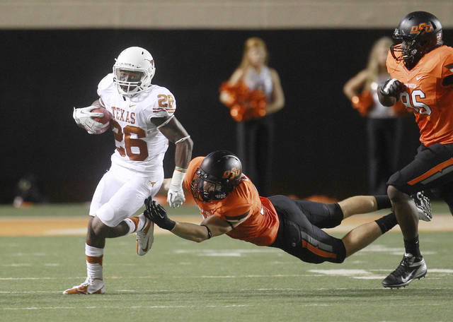 File - In this Sept. 29, 2012 file photo, Texas running back D.J. Monroe (26) avoids a tackle by Oklahoma State linebacker Alex Elkins, center, during an NCAA college football game in Stillwater, Okla. A fifth-year senior, Monroe is fulfilling the promise he showed as a freshman. He has scored a touchdown in every game this season. (AP Photo/Sue Ogrocki, File)