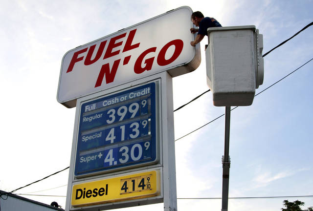 Sign worker Ray Messore, of Glocester, R.I., works on a sign next to one where gasoline prices are posted at a gas station in Pawtucket, R.I., Monday, Sept. 17, 2012. (AP Photo/Steven Senne)