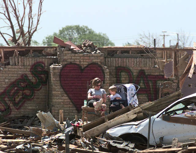 Tornado damage tour: Spectators Lee Harwell and her nephew twenty-month-old Gary Patrick-Stice wait in the remains of a house for President Bill Clinton to speak.