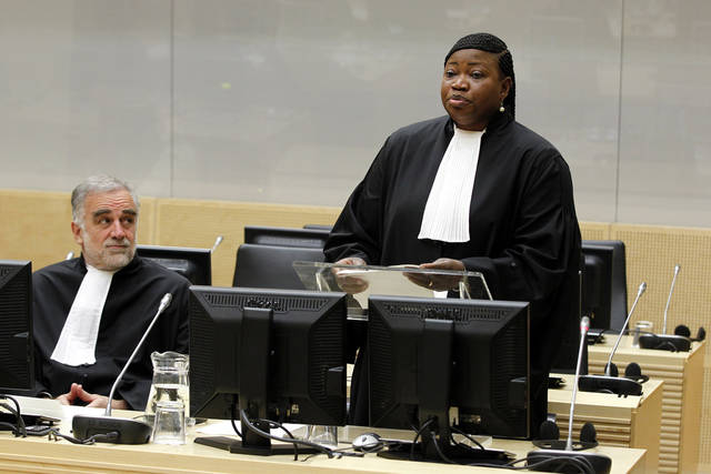 Luis Moreno-Ocampo, left, listens, as new prosecutor Fatou Bensouda, right, is holding her first speech as new prosecutor after a swearing-in ceremony at The International Criminal Court (ICC) in The Hague, Netherlands, Friday, June 15, 2012. The ICC installed Gambian war crimes lawyer Fatou Bensouda as its new prosecutor for a nine-year term on Friday. Bensounda replaces Luis Moreno-Ocampo. She will be tasked with trying to bring to justice alleged war criminals including Uganda's Joseph Kony, Libya's Seif al-Islam Gadhafi and Sudanese president Omar al-Bashir. (AP Photo/Bas Czerwinski, Pool)