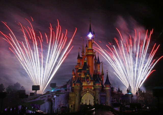 FILE - In this March 31, 2012 file photo, a firework display lights up the castle of Sleeping Beauty in Disneyland's theme park in Marne-la-Vallee, east of Paris. The Walt Disney Co. said Thursday Nov. 8, 2012, that its net income in the latest quarter rose 14 percent thanks to an uptick in revenue driven by higher consumer spending at its theme parks and on its cruise ships. (AP Photo/Michel Spingler, File)