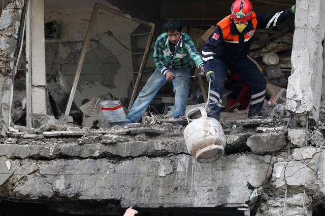 Police forensic officers and Umit Celik, left,  search for the body of Celik's sister, Aysegul Kirac, 23, in the debris of a destroyed shop two days after Saturday explosions that killed tens of people  in Reyhanli, near Turkey's border with Syria, Monday, May 13, 2013. The bombings on Saturday marked the biggest incident of cross-border violence since the start of Syria's bloody civil war and has the raised fear of Turkey being pulled deeper into the conflict.(AP Photo/Burhan Ozbilici)