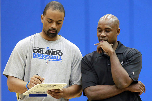 Orlando Magic assistant coach Wes Unseld Jr., left, and head coach Jacque Vaughn go over plays during NBA basketball training camp in Orlando, Fla., Wednesday, Oct. 3, 2012. (AP Photo/John Raoux)
