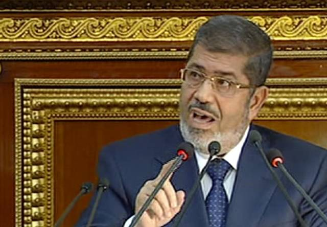 In this image made from Egyptian State Television, Egyptian President Mohammed Morsi speaks at the Shura Council, the country's upper house of parliament, in Cairo, Saturday, Dec. 29, 2012.(AP Photo/Egyptian State TV)