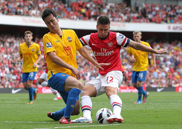 Arsenal's Olivier Giroud, right, battles for the ball with Southampton's Maya Yoshida during the English Premier League soccer match at the Emirates Stadium, London, Saturday Sept. 15, 2012. Arsenal won the match 6-1. (AP Photo/PA, Sean Dempsey) UNITED KINGDOM OUT