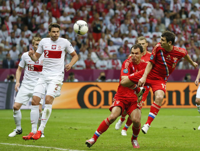 Russia's Alan Dzagoyev scores by his teammate Sergei Ignashevich and Poland's Damien Perquis, left, and Sebastian Boenisch during the Euro 2012 soccer championship Group A match between Poland and Russia in Warsaw, Poland, Tuesday, June 12, 2012. (AP Photo/Matt Dunham)
