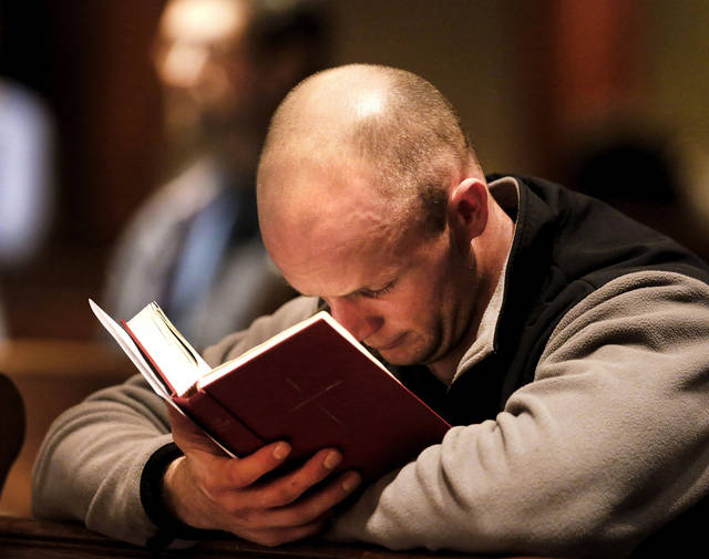 Samuel Owens, of Oklahoma City, holds a hymnal as he prays silently at a remembrance  service in Oklahoma City for those who died -- including 20 young students -- Friday in shooting at a school  in Newtown, Conn. Photo by Jim Beckel, The Oklahoman