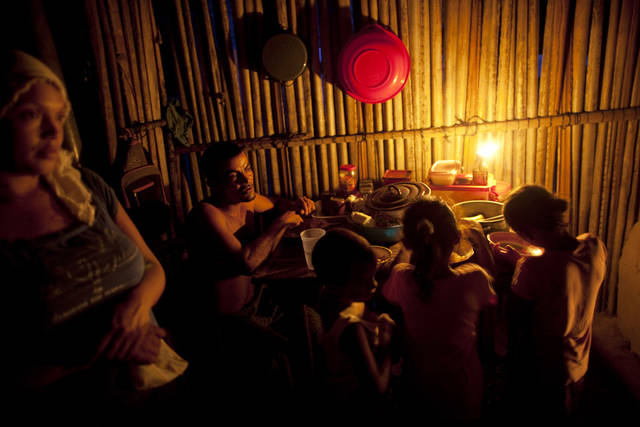 In this May 5, 2012 photo, a family eats dinner by candlelight in La Confianza, Honduras, a city developed from land seized by small-scale farmers from one of Honduras' richest men. The collection of tin-and-wood shacks boasts a health center, a school, a meeting hall, and a store. The land seizure has spawned a violent land conflict between the farmers and owner, billionaire Miguel Facusse, that has killed at least 63 people, mostly peasants, in the last three years in the Bajo Aguan Valley. (AP Photo/Rodrigo Abd)