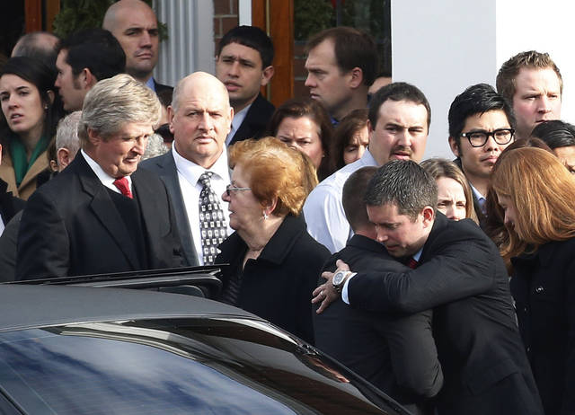 A man, bottom right, hugs Richard Rekos following funeral services for his daughter, Jessica Rekos, at St. Rose of Lima Roman Catholic Church, Tuesday, Dec. 18, 2012, in Newtown, Conn. Jessica Rekos, 6, was killed when Adam Lanza walked into Sandy Hook Elementary School in Newtown, Conn., Dec. 14, and opened fire, killing 26 people, including 20 children, before killing himself. (AP Photo/Julio Cortez) ORG XMIT: CTJC123