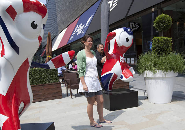 In this image taken Tuesday, May 29, 2012, people pose for photographs beside the London 2012 Olympic games mascots in a shopping mall next to the Olympic Park as final preparations are made ahead of the London games, in east London. With just 5 weeks until the July 27 opening ceremony, many Londoners remain ambivalent about the city's ability to host an event that makes them proud. Above all, they're convinced that the city's creaking, unreliable, century-old subway system will let things down. (AP Photo/Alastair Grant)