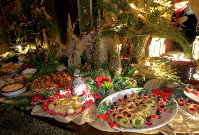 The dining room table was filled with holiday goodies from fudge to sandwiches and dips  and cheese trays. Gold Christmas trees and vases of gold poinsettias, branches and greenery with gold berries served as the centerpiece. Huge poinsettia  plants flanked the front door and the fireplace. (Photo by Helen Ford Wallace).