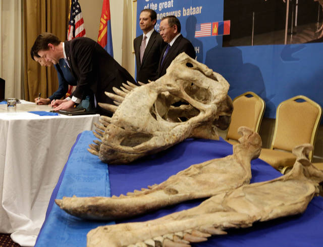 Mongolia's Minister of Culture, Sport and Tourism Oyungerel Tsedevdamba, left, and Immigration and Customs Enforcement Director John Morton, second left, second left, sign a repatriation certificate to return a Tyrannosaurus bataar skeleton, in New York,  Monday, May 6, 2013. The 70-million-year-old fossil was looted from the Gobi Desert and illegally smuggled into the U.S. It was seized by Immigration and Customs Enforcement agents in New York. Also attending the ceremony are U.S. Attorney Preet Bharara, third left, and Chief of the office of the President of Mongolia Tsagaan Puntsag. (AP Photo/Richard Drew)