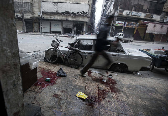 In this Monday, Dec. 3, 2012 photo, a Syrian man runs for cover during heavy fighting between Free Syrian Army fighters and government forces in Aleppo, Syria. (AP Photo/Narciso Contreras)