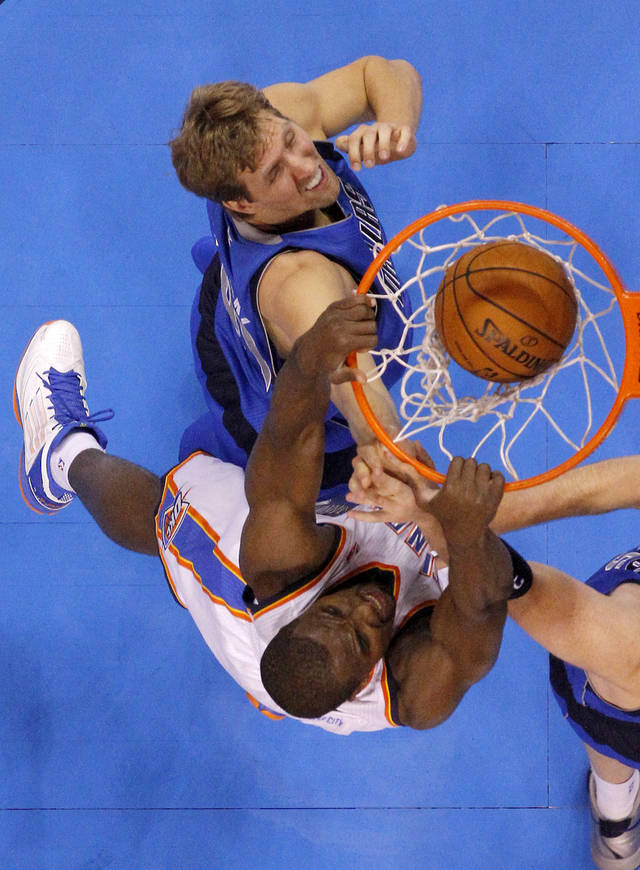 Oklahoma City's Serge Ibaka (9) dunks the ball beside Dallas' Dirk Nowitzki (41) during an NBA basketball game between the Oklahoma City Thunder and the Dallas Mavericks at Chesapeake Energy Arena in Oklahoma City, Thursday, Dec. 27, 2012.  Oklahoma City won 111-105. Photo by Bryan Terry, The Oklahoman