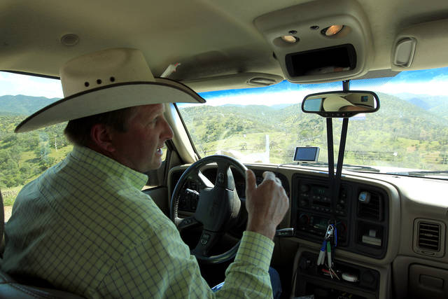 In this Friday, Aug. 10, 2012 photo, rancher Dan Bell, who owns a 35,000-acre cattle ranch along the border between the United States and Mexico, drives around as he checks out part of his property, in Nogales, Ariz. When Bell drives through his ranch, he speaks of the hurdles that the Border Patrol faces in his rolling green hills of oak and mesquite trees: The hours it takes to drive to some places, the wilderness areas that are generally off-limits to motorized vehicles, and the environmental reviews required to extend a dirt road. (AP Photo/Ross D. Franklin)