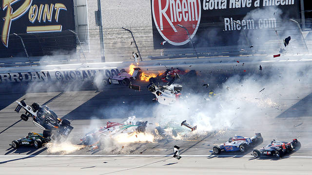 Dan Wheldon, in air at left, crashes during a wreck that involved 15 cars during the IndyCar Series' Las Vegas Indy 300 on Sunday. Wheldon died following the crash. AP Photo