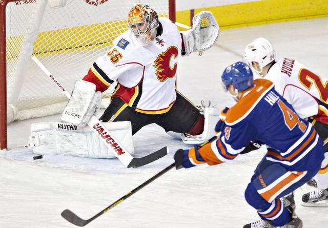 Calgary Flames goalie Joey MacDonald, left, makes the save on Edmonton Oilers' Taylor Hall (4) as Flames' Jiri Hudler, right, defends during first-period NHL hockey game action in Edmonton, Alberta, Saturday, April 13, 2013. (AP Photo/The Canadian Press, Jason Franson)