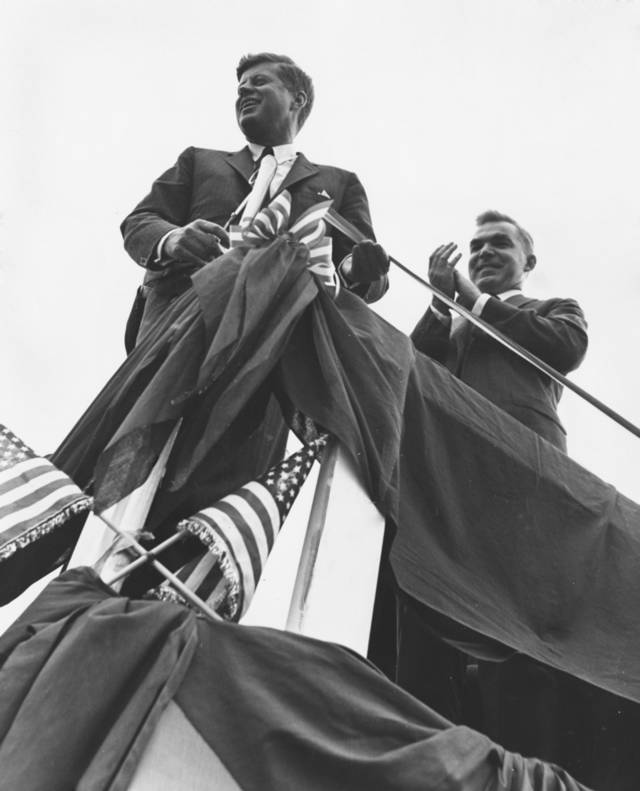 ROBERT S. KERR / U.S. SENATOR / PRESIDENT JOHN F. KENNEDY / STATE VISIT, OCTOBER 29, 1961:  SCISSORS IN HAND, Kennedy prepares to snip the ribbon marking formal opening of the scenic route.  Disaster narrowly was averted when Sen. Kerr was reminded of the chore just as he and the president were about to leave.  Leading the applause at right is Gov. Edmondson, one of many state officials present at the unprecedented occasion.  Staff photographer unknown.  Photo undated.  Published on 10/30/1961 in The Oklahoma City Times.