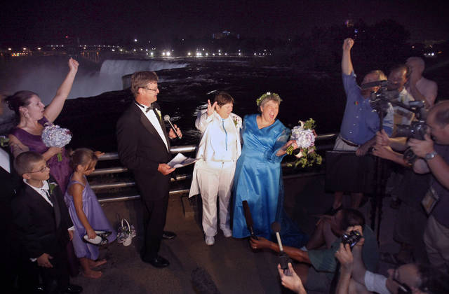 FILE - In this July 23, 2011 file photo, Kitty Lambert, right, and Cheryle Rudd celebrate their marriage in Niagara Falls, N.Y. In recent years, for economic reasons, Niagara Falls has thrown open its doors to casino gambling, gay weddings and a tightrope walk that, until laws were relaxed, would have meant arrest. It even briefly considered taking in toxic wastewater from hydraulic fracturing. On the drawing board now is a plan to entice young people to move in by paying down their student loans. (AP Photo/David Duprey, File)