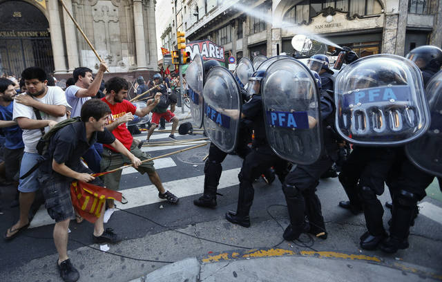 "Demonstrators and police officers clash during a protest against the acquittal of 13 people accused in the disappearance of a young woman in Buenos Aires, Argentina, Wednesday, Dec. 12, 2012. The acquittal on Tuesday of 13 people accused in the disappearance of Marita Veron, a young woman who was allegedly kidnapped and forced into prostitution for ""VIP clients,"" spread shock and outrage across Argentina on Wednesday, prompting street protests and calls by political leaders to impeach the three judges who delivered the verdict. (AP Photo/Victor R. Caivano)"