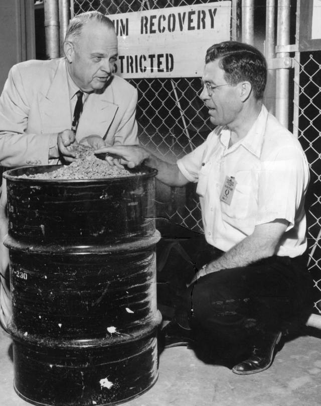 KERR-MCGEE / ROBERT S. KERR / U.S. SENATOR / DEAN McGEE:  U.S. Senator Robert S Kerr and Dean McGee, Kermac president look over a barrel of the plant's finished product--urannium ozide, also known as yellow cake. Staff Photo by Al McLaughlin
