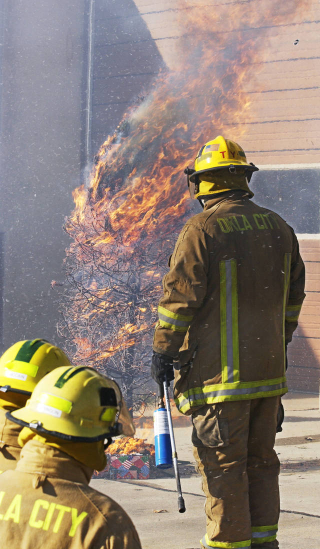 Cpl. Tom Yancey of the Oklahoma City Fire Department, right, watches as a neglected, unwatered Christmas tree burned in a master of seconds in a demonstration in 2004.  The Oklahoman Archives