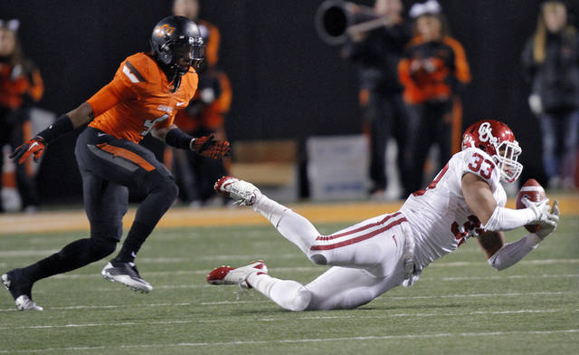 Oklahoma's Trey Millard (33) makes a reception in front of Oklahoma State's Justin Gilbert (4) during the Bedlam college football game between the Oklahoma State University Cowboys (OSU) and the University of Oklahoma Sooners (OU) at Boone Pickens Stadium in Stillwater, Okla., Saturday, Dec. 3, 2011. Photo by Chris Landsberger, The Oklahoman
