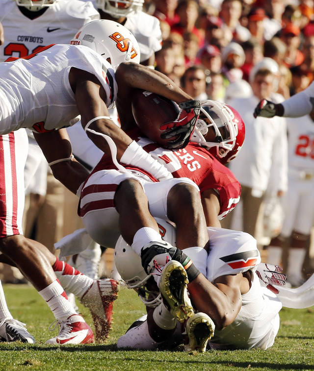 Oklahoma's Justin Brown (19) is brought down by Oklahoma State's Justin Gilbert (left) and Shamiel Gary (7) during the Bedlam college football game between the University of Oklahoma Sooners (OU) and the Oklahoma State University Cowboys (OSU) at Gaylord Family-Oklahoma Memorial Stadium in Norman, Okla., Saturday, Nov. 24, 2012. Photo by Steve Sisney, The Oklahoman