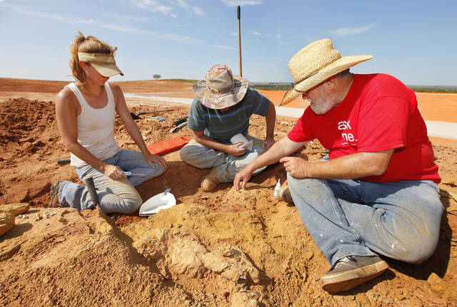 Amy Cojeen and David Boling, archaeologists with Cojeen Archaeological Services, and paleontologist Kyle Davies, right, fossil preparator with the Sam Noble Oklahoma Museum of Natural History, prepare a fossilized bone for removal form pit C on an Apache Corp. drilling site at the Packsaddle Wildlife Management Area in Ellis County south of Arnett Thursday, Aug. 22, 2013.  Teeth and bone fossils found at the site included those from prehistoric camels and horses. Photo by Paul B. Southerland, The Oklahoman <strong>PAUL B. SOUTHERLAND - PAUL B. SOUTHERLAND</strong>