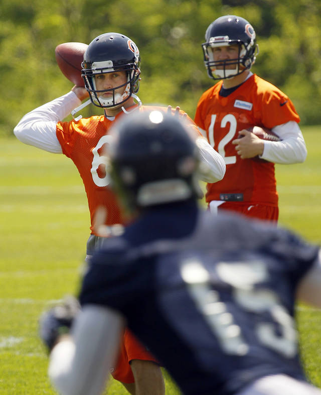 FILE - This May 23, 2012 file photo shows Chicago Bears quarterback Jay Cutler, left, throwing a pass to wide receiver Brandon Marshall, as quarterback Josh McCown, (12) watches during NFL football practice in Lake Forest, Ill. An explosive tandem in Denver, Cutler and Marshall are reunited with the Chicago Bears. (AP Photo/Charles Rex Arbogast, File)