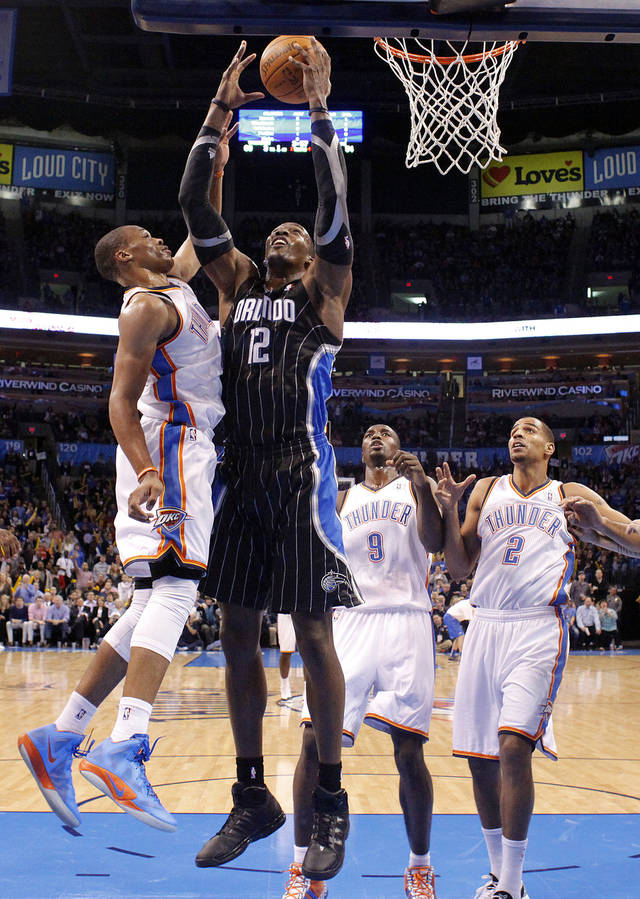 Oklahoma City Thunder's Russell Westbrook (0) fights Orlando Magic's Dwight Howard (12) for a rebound during the opening day NBA basketball game between the Oklahoma CIty Thunder and the Orlando Magic at Chesapeake Energy Arena in Oklahoma City, Sunday, Dec. 25, 2011. Photo by Sarah Phipps, The Oklahoman