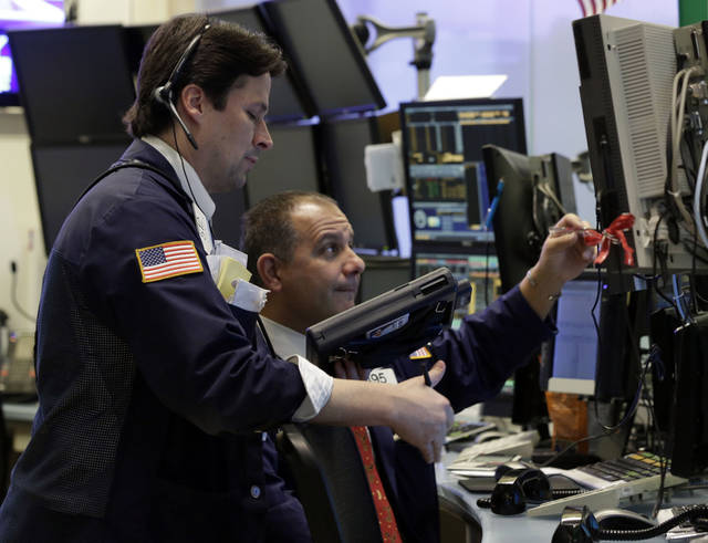 "In this Friday, Dec. 14, 2012,  photo, Traders Patrick McKeon, left, and Joel Lucchese work on the floor of the New York Stock Exchange. Stocks rose modestly Monday, Dec. 17, 2012, on Wall Street. Investors were encouraged by signs of progress in talks to avoid the ""fiscal cliff"" of tax increases and government spending cuts set to take effect in two weeks and a prediction of steady economic growth next year. (AP Photo/Richard Drew)"