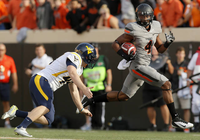 Oklahoma State's Justin Gilbert (4) gets past West Virginia's Corey Smith (44) on a kickoff return for a touchdown in the first quarter during a college football game between Oklahoma State University (OSU) and West Virginia University (WVU) at Boone Pickens Stadium in Stillwater, Okla., Saturday, Nov. 10, 2012. Photo by Nate Billings, The Oklahoman