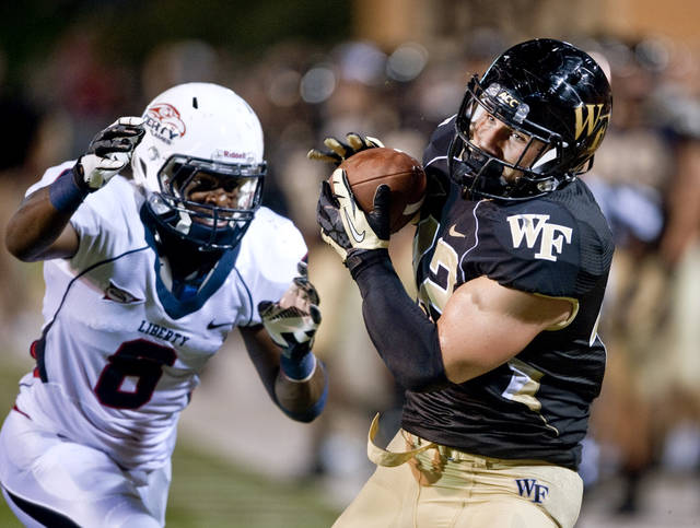 Wake Forest's Tommy Bohanon, right, catches a pass near the end zone as Liberty's Brent Vinson, right, tries to tackle him during the second half of an NCAA college football game in Winston-Salem Saturday, Sept. 1, 2012. Wake Forest defeated Liberty 20-17. (AP Photo/Winston-Salem Journal, Lauren Carroll)