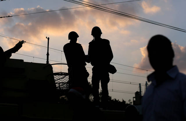Egyptian army soldiers stand on top of their tank as the sun sets outside the presidential palace, background, in Cairo, Egypt, Saturday, Dec. 8, 2012. Egypt's military warned Saturday of 'disastrous consequences' if the crisis that sent tens of thousands of protesters back into the streets is not resolved, signaling the army's return to an increasingly polarized and violent political scene.(AP Photo/Hassan Ammar)
