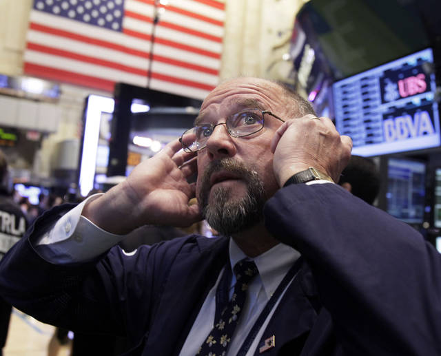 FILE- In this Sept. 20, 2012, file photo Trader Frederick Reimer works on the floor of the New York Stock Exchange. World stock markets fell Tuesday, Sept. 25, weighed down by a host of concerns about the global economy. (AP Photo/Richard Drew, File)