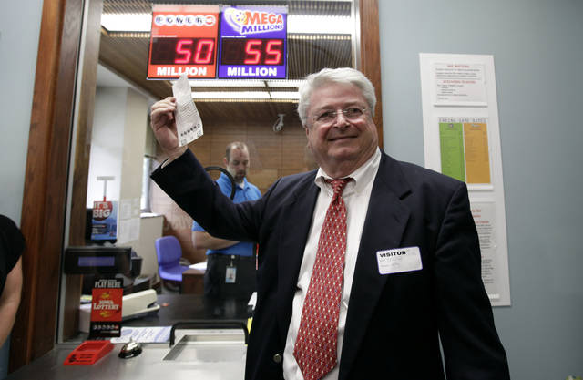 Attorney Joe Day holds up the winning $241 million Powerball ticket before it is cashed in for his clients, a group of workers from the Quaker Oats plant in Cedar Rapids, Iowa, at the Iowa Lottery headquarters, Wednesday, June 20, 2012, in Des Moines, Iowa. Lottery spokeswoman Mary Neubauer says one of the workers bought the winning ticket for the group for the June 13 drawing and the winnings will be split 20 ways.(AP Photo/Charlie Neibergall)