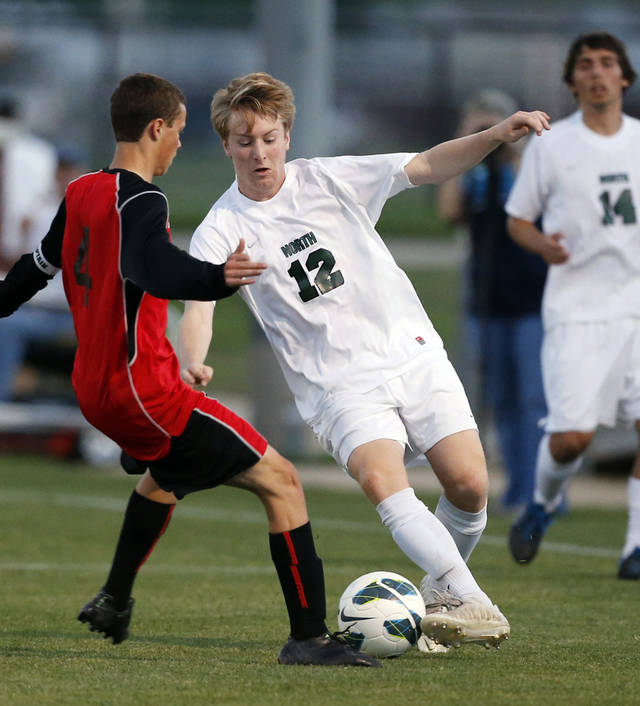 Cole Johnson (12) tries to go around Ryan Hill (4) as Norman North plays Yukon in a high school soccer playoff game at Norman North on Tuesday, April 30, 2013 in Norman, Okla.  Photo by Steve Sisney, The Oklahoman