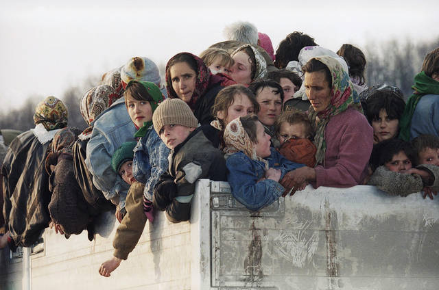 "FILE In this Monday March 29, 1993 file photo evacuees from the besieged Muslim enclave of Srebrenica, packed on a truck en route to Tuzla, pass through Tojsici, 56 miles north of Sarajevo. More than 2,300 evacuees left Srebrenica on U.N. trucks for Tuzla. The indictment against Ratko Mladic, who went on trial Wednesday May 16, 2012 at the U.N. war crimes tribunal in the Hague, Netherlands, holds the former Bosnian Serb army commander ""individually criminally responsible for planning, instigating, ordering and/or aiding and abetting the crimes charged in this indictment."" Mladic is charged with 11 counts of genocide, crimes against humanity and violations of the laws and customs of war. Between July 1995 and November 1995, Mladic participated in the ""elimination"" of the Bosnian Muslims in the eastern enclave of Srebrenica by killing the men and boys, and forcibly removing the women, young children and some elderly men. Some 7,000 people were killed which is the worst carnage in Europe since World War II.(AP Photo/Michel Euler)"