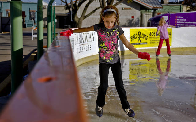Halle McFarlane works to get her balance along the rail at the Edmond outdoor ice skating rink on Sunday, Dec. 2, 2012, in Edmond, Okla.   Photo by Chris Landsberger, The Oklahoman
