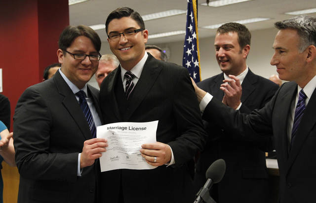 Brendon K. Taga, left, and partner Jesse Page display their marriage license issued by King County Executive Dow Constantine, right, just after midnight, Thursday, Dec. 6, 2012, in Seattle. Taga and Page were second in line. Constantine began issuing the licenses immediately upon certification of the November election that passed Referendum 74. (AP Photo/Elaine Thompson)