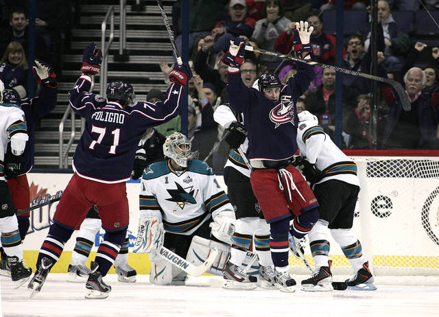 Columbus Blue Jackets' Brandon Dubinsky (17) scores against San Jose Sharks goalie Thomas Greiss (1) during the first period of an NHL hockey game, Monday, Feb. 11, 2013, in Columbus, Ohio. Rushing in to celebrate is Blue Jackets' Nick Foligno. (AP Photo/Mike Munden)