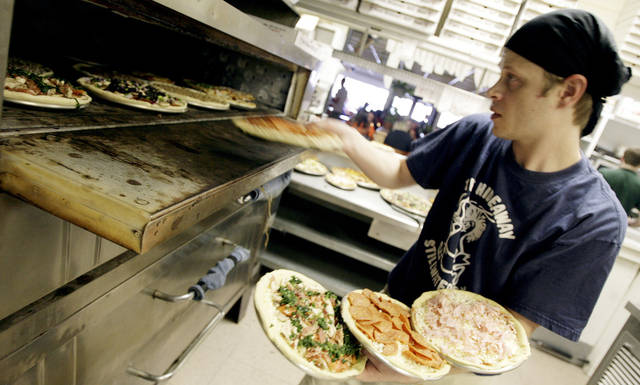 Pizza cook Justin Shenold puts pizzas in the oven at The Hideaway restaurant, in Stillwater, Okla., Friday, Jan. 19, 2007. By Matt Strasen, The Oklahoman