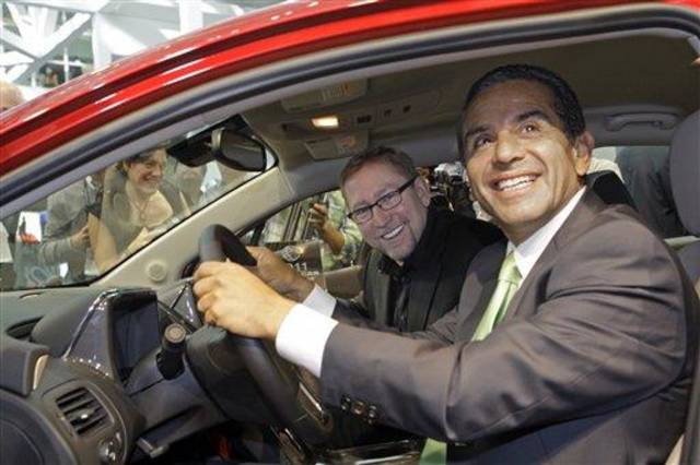 Los Angeles Mayor Antonio Villaraigosa is behind the wheel with Joel Ewanick, General Motors Co. vice president for U.S. Marketing, in the Chevy Volt, 2011 Green Car of the Year, presented by Green Car Journal, at the L.A. Auto Show Thursday, Nov. 18, 2010.   (AP Photo/Reed Saxon)