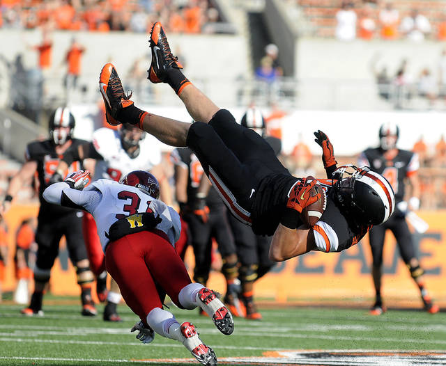 Oregon State's Connor Hamlett (89) flips over Eastern Washington's T.J. Lee (31) while leaping to catch a pass in the third quarter Saturday Aug. 31, 2013 in Corvallis, Ore. (Amanda Cowan | Corvallis Gazette-Times)
