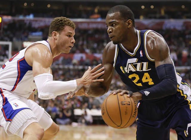 Utah Jazz forward Paul Millsap, right, drives to the basket around Los Angeles Clippers forward Blake Griffin during the first half of an NBA basketball game in Los Angeles, Saturday, Feb. 23, 2013. (AP Photo/Chris Carlson)