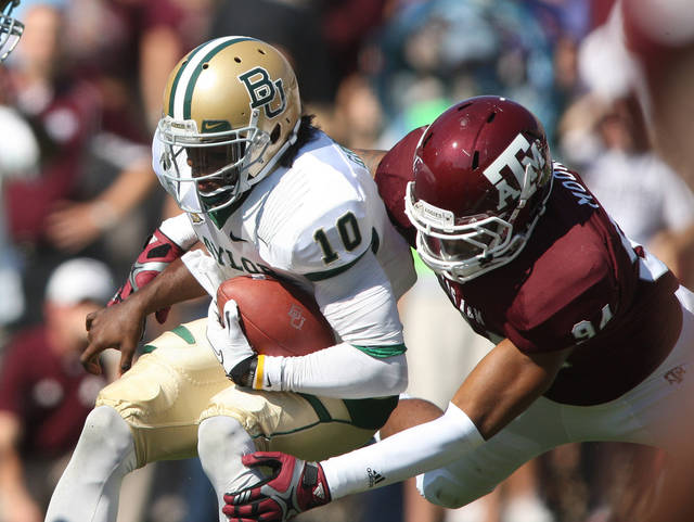 Texas A&M's Damontre Moore (94) sacks Baylor's Robert Griffin III during the first half of an NCAA college football game Saturday, Oct. 15, 2011, in College Station, Texas. (AP Photo/Jon Eilts) ORG XMIT: TXJE103