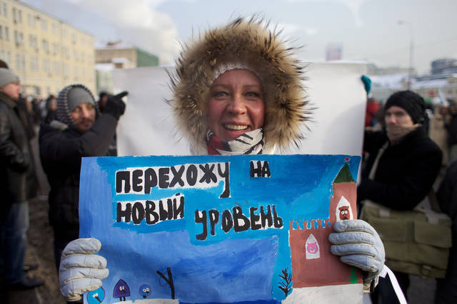 "In this Saturday, Feb. 4, 2012 photo, Tatyana Lazareva, 46, a television presenter, holds a poster reading ""move on to the next level"" as she poses in front of a white canvas placed in the middle of the crowd at a massive protest against Prime Minister Vladimir Putin's rule in Bolotnaya square in Moscow. Despite temperatures plunging to minus 20 C (minus 4 F), thousands of Russians took to the streets of Moscow to challenge Putin's bid to reclaim presidency in March. (AP Photo/Alexander Zemlianichenko)"