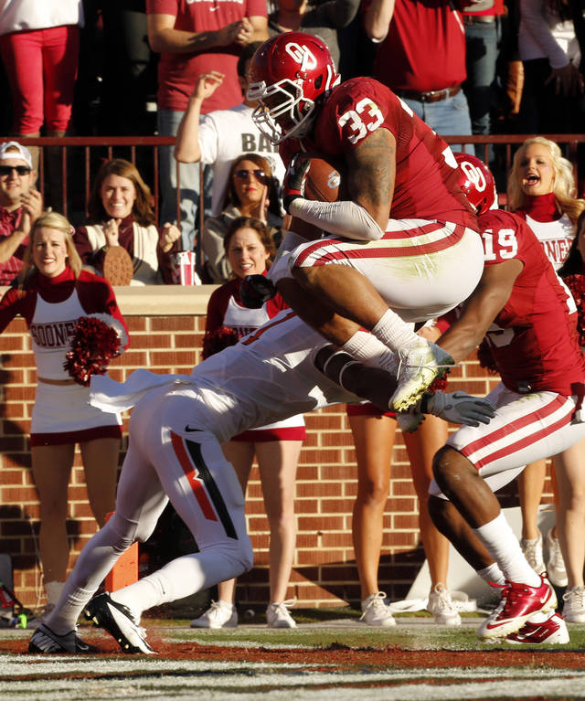 Oklahoma's Trey Millard (33) leaps over defender Kevin Peterson (1) for a touchdown during the Bedlam college football game between the University of Oklahoma Sooners (OU) and the Oklahoma State University Cowboys (OSU) at Gaylord Family-Oklahoma Memorial Stadium in Norman, Okla., Saturday, Nov. 24, 2012. Photo by Steve Sisney, The Oklahoman